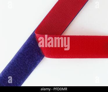 Blue and red strips of velcro partially fastened together, close up - Stock Photo
