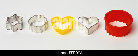 Selection of differently shaped plastic and metal pastry cutters, elevated view. - Stock Photo
