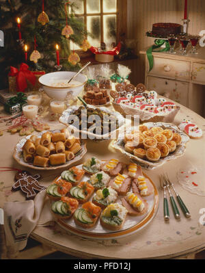 Table decorated for Christmas, with tree and candles, and selection of cookies, gingers, caramels, canapes, toad in the hole, meatballs. - Stock Photo