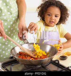 Girl adding sweetcorn with spoon, alongside woman stirring onions and red bell peppers in frying pan, bowls of sweetcorn, vinegar and honey on kitchen worktop, close-up - Stock Photo