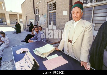 Baghdad, Iraq - 15 October 1995 - Iraqi voters at the polls during the Presidential referendum, where the single candidate (Saddam Hussein) is on the paper ballot asking 'Do you approve of President Saddam Hussein being President of the Republic?   He would go on to win 99.96% of the vote.  Iraqi's find it harder to maintain a decent standard of living due to the strict UN sanctions imposed during the 1990s because of Iraq's invasion of Kuwait in 1990. - Stock Photo