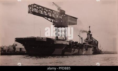 A view of the HMS Illustrious docked at Norfolk Navy Yard in May 1941. The Royal Navy Aircraft Carrier sustained severe damage from German dive bombers in Malta. Since British shipyards were under near daily attack from Luftwaffe aircraft, she steamed across the Atlantic to Norfolk Navy Yard and arrived in May 1941 for repairs and a refit. Her repairs were completed in December 1941, shortly before the US entered WWII; she was the first of nearly 140 Royal Navy Ships to be built or serviced at the shipyard during the war. - Stock Photo