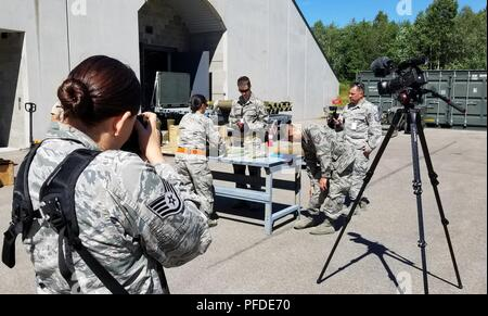 Staff Sgt. Bobbie Reynolds (left) and Master Sgt. Wolfram Stumpf (back right), Public Affairs Specialists from the 140th Wing, Colorado Air National Guard, document munitions troops as they build bombs for training missions during Saber Strike 18 at Amari Air Base, Estonia, June 4, 2018.  Saber Strike 18 is the eighth iteration of the long-standing U.S. Army Europe-led cooperative training exercise designed to enhance interoperability among allies and regional partners. This year's exercise will take place June 3-15, focusing on improving land and air operational capabilities with an additiona - Stock Photo
