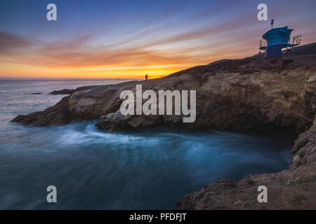 Stunning long-exposure view of smooth waves crashing into rock formations and lifeguard station at sunset, Sequit Point, Leo Carrillo State Beach, Mal - Stock Photo