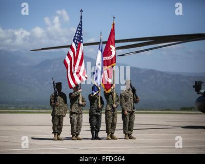 A multinational color guard comprised of Marines with Special Purpose Marine Air-Ground Task Force - Southern Command and a Honduran Army soldier carry colors during an opening ceremony on Soto Cano Air Base, Honduras, to mark the beginning of SPMAGTF-SC deployment to Latin America and the Caribbean, June 11, 2018. The Marines and sailors of SPMAGTF-SC will conduct security cooperation training and engineering projects alongside partner nation military forces in Central and South America during their deployment. The unit is also on standby to provide humanitarian assistance and disaster relief - Stock Photo