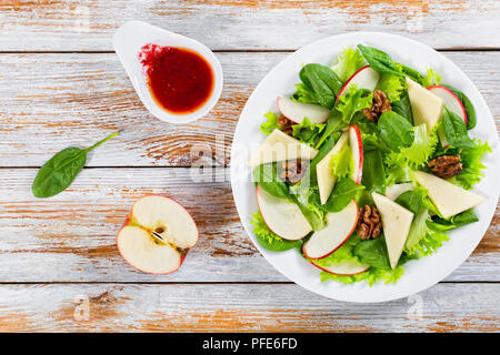 delicious autumn  salad: apple, spinach, cheese slices, lettuce, walnuts, cranberry on white dish  on chopping board with knife and fork, berry dressi - Stock Photo