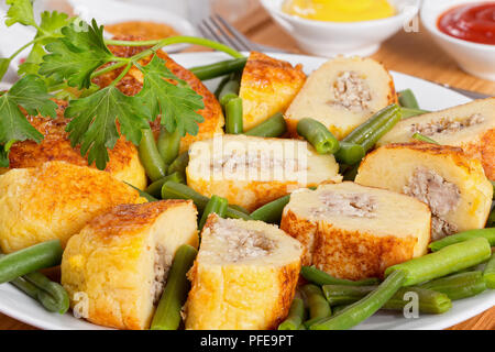 delicious Italian Potato Pancakes from mashed potato filled  with ground chicken meat with green beans on white platter, mustard and tomato sauce on b - Stock Photo