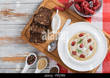 delicious Beer and cream spicy Soup with Kielbasa Sausage, dill. and cheese in wide rim plate on chopping board with spices and rye bread, authentic r - Stock Photo