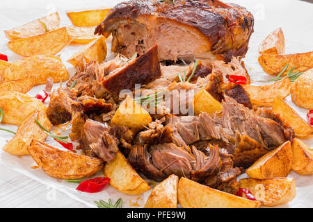 fried Potato wedges and Big Piece of Slow Cooked Oven-Barbecued Pulled Pork  shoulder, cooking according authentic recipe, on parchment paper with ros - Stock Photo
