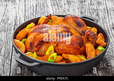 roast whole chicken with fried potato wedges and leek in cast iron pan on old wooden boards, close-up, view from above - Stock Photo