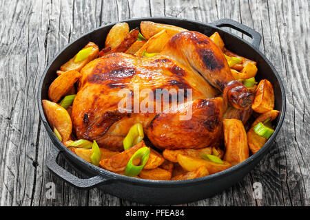 golden crispy skin chicken grilled in oven with potato wedges and leek in cast iron pan on old wooden boards, close-up, view from above - Stock Photo
