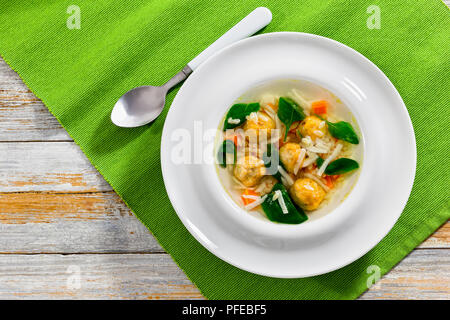 italian wedding soup with meatballs, small pasta risini,spinach and vegetables cooked according to authentic recipe, view from above - Stock Photo