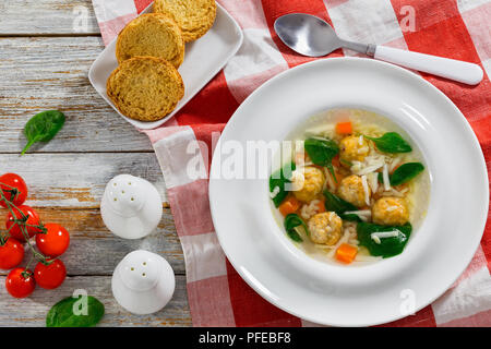 italian wedding soup with meatballs in white wide rim bowl on table cloth, salt and pepper shakers, crostini, fresh green spinach leaves and tomatoes  - Stock Photo