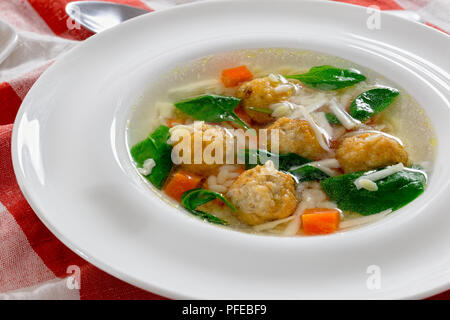 delicious wedding soup with meatball, carrots and spinach in white wide rim bowl with spoon on table cloth, authentic recipe, close-up - Stock Photo