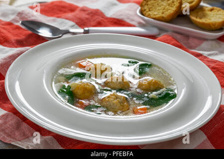 delicious wedding soup with meatball, risini pasta, carrots and spinach in white wide rim bowl with spoon on table cloth, authentic recipe, close-up - Stock Photo