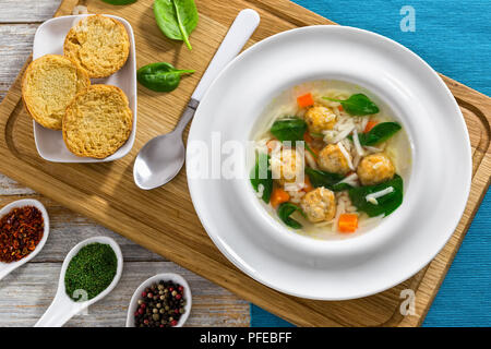 delicious wedding soup with meatball, risini pasta, carrots and spinach in white wide rim bowl with spoon on chopping board,  toasted bread crostini a - Stock Photo
