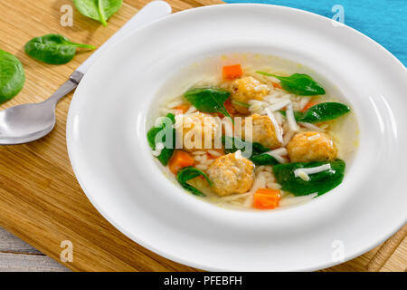 delicious chicken soup with meatball, risini pasta, carrots and spinach in white wide rim bowl with spoon on chopping board,  view from above, close-u - Stock Photo
