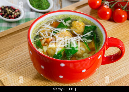 delicious italian wedding chicken soup with meatballs, small pasta risoni,spinach and vegetables in red cup on chopping board, view from above, close- - Stock Photo