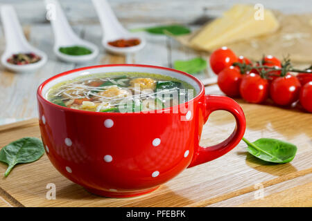 delicious italian wedding chicken soup with meatballs, small pasta risoni,spinach and vegetables in red cup on chopping board,  close-up - Stock Photo