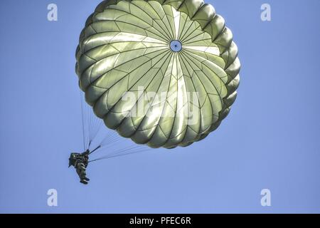 An American paratrooper from the 173rd Airborne Brigade descends onto Iron Mike Drop Zone in Sainte Mere Eglise, France wearing a German parachute.  The American paratrooper is jumped from a German aircraft to earn his foreign jump wings.  Paratroopers from France, Holland, Germany, Romania and the United States are participating an a commemorative parachute jump for D-Day 74. - Stock Photo