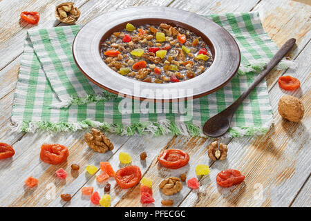 Sweet wheat kutia with nuts, poppy seeds, dried fruits. succade and honey in clay bowl with spoon on kitchen cloth on wooden planks. with ingredients  - Stock Photo