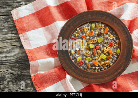 kutya or Sweet Wheat Berry Pudding, traditional Christmas dish in clay rustic bowl on table cloth on dark wooden table, view from above - Stock Photo