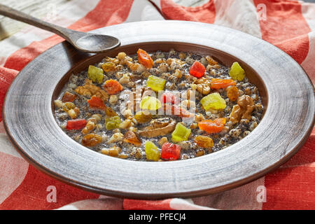 kutya or Sweet Wheat Berry Pudding traditional Christmas dish in clay rustic bowl with wooden spoon on table cloth on dark wooden table, view from abo - Stock Photo