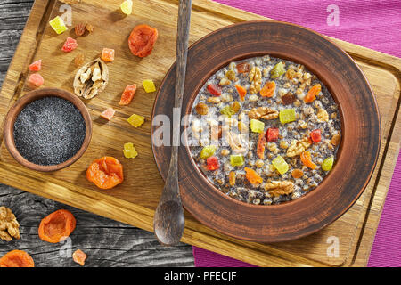 Traditional Christmas slavic dish kutia in ceramic bowl on chopping board with ingredients, view from above - Stock Photo