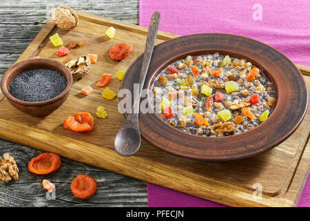 Traditional Christmas slavic dish kutia in ceramic bowl on chopping board with wooden spoon and ingredients on background, view from above, close-up - Stock Photo