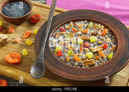 Traditional Christmas slavic dish kutia with poppy seeds, boiled wheat and dried fruits in ceramic bowl on chopping board with ingredients, authentic  - Stock Photo