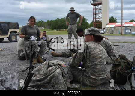 New York Army National Guard Soldiers, assigned to the 3rd Battalion, 142nd Aviation, clean M240s on Fort Drum, N.Y., June 3rd, 2018. Following Ariel Gunnery training, Soldiers from the 3-142 had to conduct weapons maintenance before departing from Fort Drum. (N.Y. Army National Guard - Stock Photo