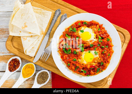 shakshuka - eggs,bell pepper, chili, tomato sauce and spices on white dish with flatbread on chopping board. cumin, curcuma, pepper flakes in ceramic  - Stock Photo