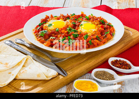 shakshuka - sunny-side-up eggs,bell pepper, chili, tomato sauce and spices on white dish with flatbread on chopping board. cumin, curcuma, pepper flak - Stock Photo