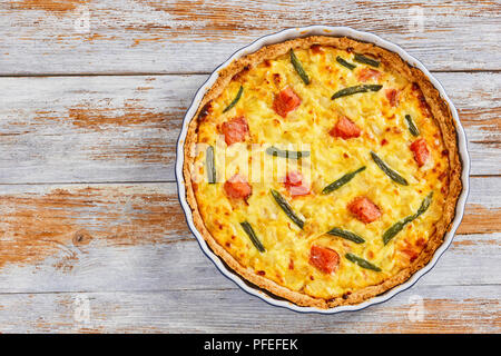 delicious quiche tart stuffed with Salmon,green bean and Emmental cheese, cream, onion and eggs in baking dish on old white wooden table, view from ab - Stock Photo