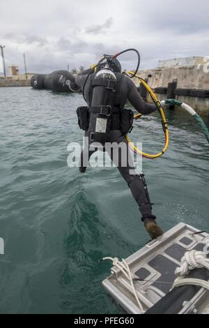 Construction Mechanic 2nd Class Andersen Gardner, from Fairport New York, attached to Underwater Construction Team (UCT) 2 performs dive operations in Apra Harbor, Guam June 6, 2018. UCT 2 specializes in the construction, inspection, maintenance, and repair of underwater and waterfront facilities in support of the Pacific Fleet. - Stock Photo