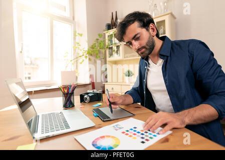 Graphic designer working on digital tablet. Freelancer working at home. - Stock Photo