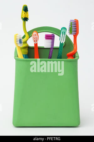 Green plastic pot holding six toothbrushes. - Stock Photo