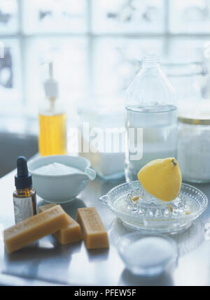 Utensils for natural cleaning, including half lemon on glass squeezer, blocks of beeswax, vinegar, liquid soap, baking soda, salt, essential oils - Stock Photo
