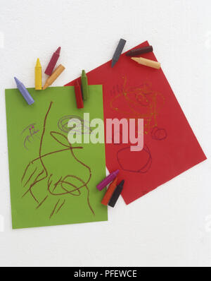 Doodles on pieces of green and red paper, with a selection of coloured crayons - Stock Photo
