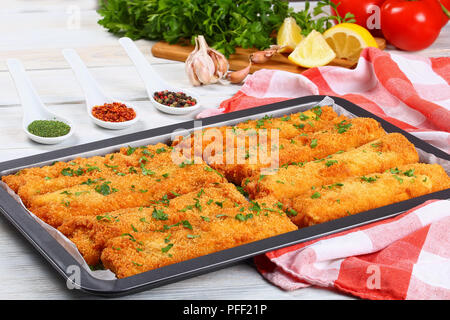 delicious Crispy Chicken and cheese Tortilla Roll Ups baked in oven with bread crumbs in baking dish on wooden table, view from above - Stock Photo
