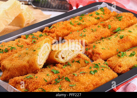 delicious Crispy Chicken cheese breaded taquitos in baking dish on wooden table with pieces of parmesan cheese on background, view from above, close-u - Stock Photo
