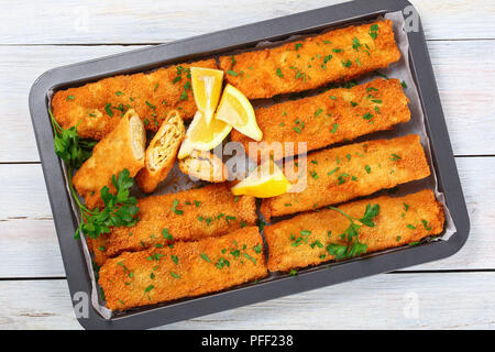 delicious Crispy breaded taquitos stuffed with Chicken and grated cheese with lemon slices and parsley in baking dish on wooden table, view from above - Stock Photo