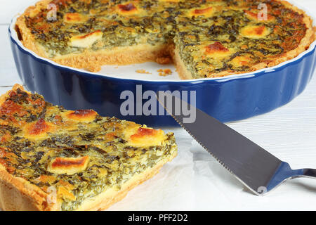 Quiche Florentine with spinach, cheese, eggs and spices  cut in slices in baking dish, piece of tart on paper on white wooden table with spatula, clos - Stock Photo