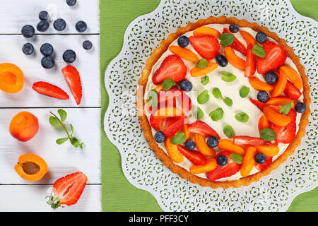 fruit cake layered with cheese yogurt custard beautifully topped with fresh strawberries, apricot and blueberries on paper napkin on white table with  - Stock Photo