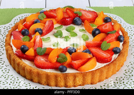 fruit cake with cheese yogurt custard beautifully topped with fresh strawberries, apricot and blueberries on paper napkin on white table with fruits a - Stock Photo