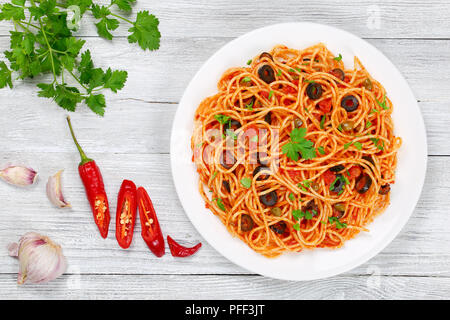 Delicious Spaghetti alla puttanesca with capers, olives, anchovies, tomato sauce sprinkled with parsley on white plate on wooden table with ingredient - Stock Photo