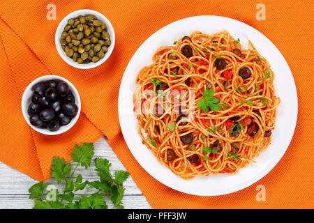 Delicious Spaghetti alla puttanesca with capers, olives, anchovies, tomato sauce sprinkled with parsley on white plate on table mat with olive and cap - Stock Photo