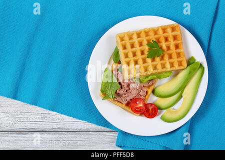 delicious salted belgian waffles sandwich with avocado slices, turkey liver pate, lettuce, spinach and parsley on white plate with cherry tomatoes, he - Stock Photo