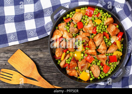 one pot dish - delicious stir fried meat chunks with green peas, onion, red and yellow bell peppers in stewpan with kitchen towel and spatulas, on old - Stock Photo