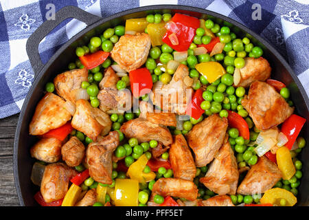 one pot dish - delicious stir fried meat chunks with green peas, onion, red and yellow bell peppers in stewpan with kitchen towel on old dark wooden t - Stock Photo